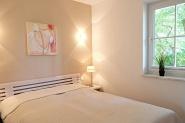 Ein gemütliches helles Schlafzimmer mit Doppelbett